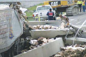 (Photos by Tim Fleischer) A Texas DPS officer looks over the area in which a pickup truck was crushed beneath the girder of the FM 2484 overpass of I-35. The accident occurred about 11:15 a.m. March 26 when a flatbed semi carrying a cherry picker hit the girders causing them to topple and fall onto vehicles on the interstate mainlanes, including a semi truck traveling in each direction. Traffic was shut down over night for crews to clean the area.