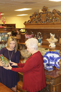 Donna Gantenbein (right) shows a rare art glass vase to a customer at Salado Creek Antiques.