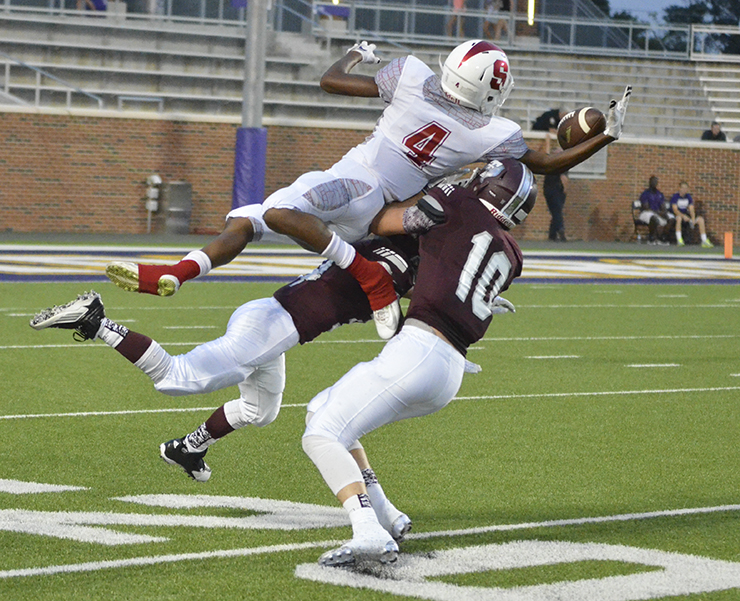 Salado wide receiver Cutter Hudgens leaps over two Troy Trojan defenders to try to catch a pass during the Eagles' 24-9 loss. Photo by Ron LeGuin